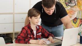 父亲显示给他的在笔记本屏幕上的儿子如何发现答复到任务慢动作的问题 股票录像