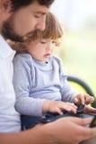 父亲显示他的小女儿如何工作在膝上型计算机 图库摄影