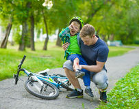父亲检查受伤的孩子跌下自行车 库存图片