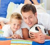 父亲橄榄球他符合儿子注意 免版税库存图片