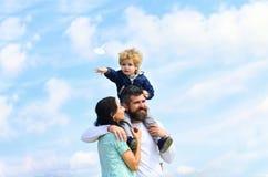 父亲母亲和儿子在公园 要作-快乐的男孩的自由使用与纸飞机 r r 库存照片