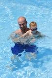 父亲池微笑的儿子游泳 免版税库存照片