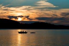 父亲渔剪影与孩子的在湖的日落的 免版税库存照片