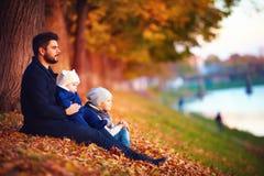 父亲画象有享受在下落的叶子中的孩子的秋天 图库摄影