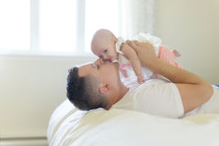 父亲画象有她的3个月大婴孩的在卧室 免版税库存照片