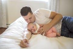 父亲画象有她的3个月大婴孩的在卧室 库存图片