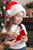 从父亲的圣诞节惊奇圣诞老人帽子的小女孩的 免版税库存照片