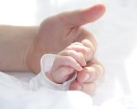 父亲的手和婴孩的微小的手 免版税库存照片
