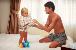 父亲穿上礼服给女儿由明亮的窗口 免版税库存图片