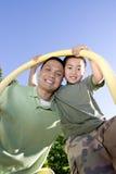 父亲突出在垂直之下的杆儿子 免版税库存图片