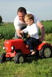 父亲红色儿子拖拉机 免版税库存图片