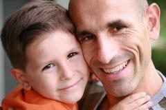 父亲纵向微笑的儿子 免版税库存照片