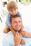 父亲纵向松弛沙发儿子 免版税库存图片