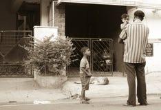 父亲背面图和他儿童等待室外 库存照片