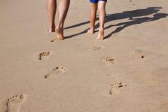 父亲脚印铺沙湿的儿子 库存照片