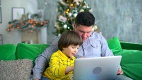 父亲膝上型计算机儿子使用 在家看有非常逗人喜爱的儿子的英俊的父亲计算机一个沙发的在背景 影视素材