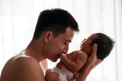 父亲节与新出生的婴孩护理的接合概念 父亲是使用和谈话与在窗口旁边的新出生的婴孩 唯一爸爸co 免版税库存图片