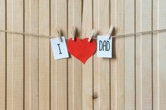 父亲节概念 与垂悬与别针的纸心脏的消息在轻的木板 E 免版税库存图片