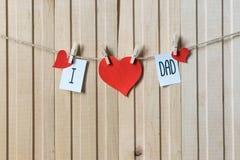 父亲节概念 与垂悬与别针的纸心脏的消息在轻的木板 ?? 图库摄影