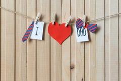父亲节概念 与纸心脏、垂悬与别针的领带和弓领带的消息在轻的木板 Copyspace ?? 库存照片