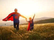 父亲节的概念 英雄超级英雄服装的爸爸和儿童女儿在日落 免版税图库摄影