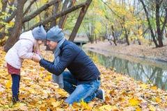 年轻父亲获得与逗人喜爱的女儿的乐趣在秋天 图库摄影