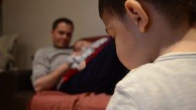 父亲藏品六个月儿子,当小孩使用与玩具时 焦点改变的射击 股票视频