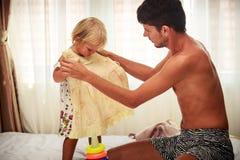父亲要试穿黄色礼服给女儿在窗口 免版税图库摄影