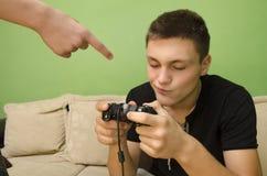 父亲警告他的孩子不打电子游戏 免版税库存照片