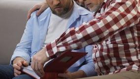 父亲讲故事对他的从家庭册页的儿子观看的照片,记忆 影视素材