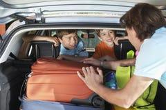 父亲谈话与被装载的汽车的男孩 免版税库存图片