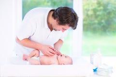 年轻父亲谈话与他新出生的小儿子 免版税库存图片