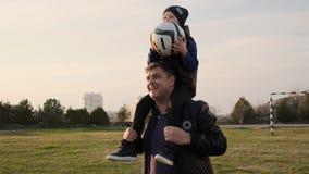 父亲跑在与他的小儿子的橄榄球场下肩膀的并且获得与他的乐趣慢动作 股票录像