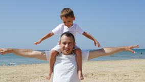 父亲运载他的他的胳膊的儿子,摇摆他的描述飞机的胳膊 休息由海的幸福家庭 影视素材