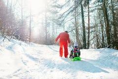 父亲运载有他的小女儿的雪撬雪slo的 免版税库存照片