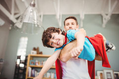 父亲运载的儿子佩带的超级英雄服装画象  库存照片