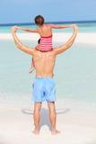 父亲运载的女儿背面图海滩假日的 库存图片