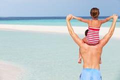 父亲运载的女儿背面图海滩假日的 免版税库存照片