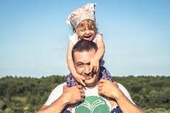 父亲逗人喜爱的女儿获得乐趣一起作为家庭在蓝天前面的生活方式画象 抱他的孩子的愉快的父亲 库存图片