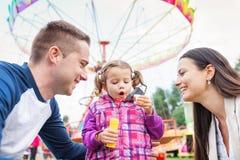 父亲,母亲,女儿吹的泡影,游乐园,乐趣fa 图库摄影