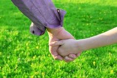 父亲` s和他的女儿手 免版税库存图片