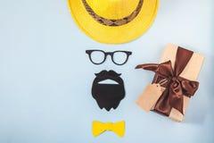 父亲` s天概念 行家样式帽子、玻璃、胡子和礼物在一张蓝色背景明信片复制空间顶视图 库存照片