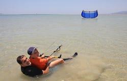 父亲kitesurfing的儿子 免版税图库摄影