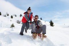 父亲sledding的儿子年轻人 免版税库存图片