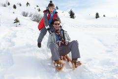 父亲sledding的儿子年轻人 免版税库存照片