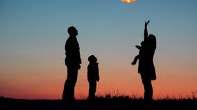 父母、孩子和婴孩现出轮廓上升的闪电天空灯笼,发布希望 股票录像