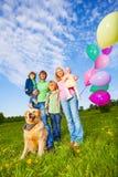 父母、孩子和狗站立与气球在公园 免版税库存图片