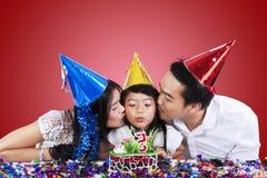 父母亲吻他们的生日聚会的孩子 免版税库存照片
