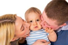 父母亲吻他的婴孩 库存照片