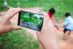 父母使用电话拍摄他们的演奏摇摆的孩子 免版税库存照片